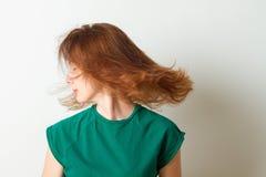 En ung kvinna som skakar hennes huvud med hennes hårflyg runt om henne i svartvitt Arkivfoto