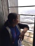 En ung kvinna som tycker om bird's, synar sikten av havet till och med fönstret Arkivfoton