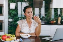En ung kvinna spenderar tid hemma, i köket och i rooen royaltyfria bilder