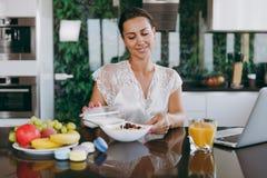 En ung kvinna spenderar tid hemma, i köket och i rooen royaltyfri foto