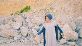 En ung kvinna står mot en bakgrund av berg och stenar med magiskt gräs tjuserska arkivfilmer