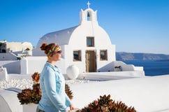 En ung kvinna står mot en vit kyrka på den berömda romantiska ön av Santorini royaltyfria bilder