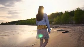 En ung kvinna strosar längs strandlinjen längs floden, nära skogen lager videofilmer