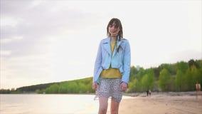 En ung kvinna strosar längs strandlinjen längs floden, nära skogen stock video