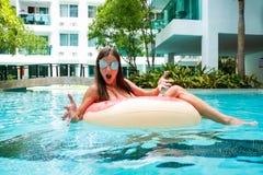 En ung kvinna sv?var p? havet i en simma cirkel En flicka kopplar av på havet på den uppblåsbara cirkeln med royaltyfri fotografi
