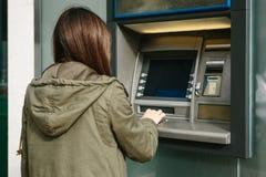 En ung kvinna tar pengar från en ATM Griper ett kort från ATMEN Finans kreditkort, tillbakadragande av pengar royaltyfri fotografi