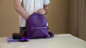 En ung kvinna tar ut innehållet av hennes purpurfärgade ryggsäck och sätter all saker på en vit tabell Innehåll av dampåsen stock video