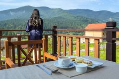 En ung kvinna tycker om ett berglandskap, medan hennes frukost kyler ner royaltyfri fotografi