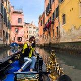 En ung kvinna tycker om en gondolritt och framställningsfotoet i kanalerna av Venedig fotografering för bildbyråer