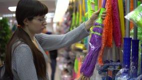 En ung kvinna väljer en färggolvmopp för att göra ren i ett lager stock video