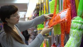 En ung kvinna väljer en färggolvmopp för att göra ren i ett lager arkivfilmer