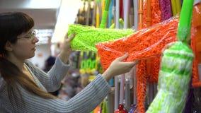 En ung kvinna väljer en färggolvmopp för att göra ren i ett lager lager videofilmer