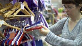 En ung kvinna väljer kulöra hängare för ett lag för kläder i ett lager arkivfilmer