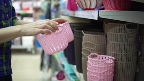 En ung kvinna väljer och köper plast- korgar för saker i supermarket lager videofilmer