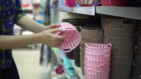 En ung kvinna väljer och köper plast- korgar för saker i supermarket stock video