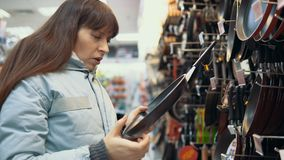 En ung kvinna väljer en panna på lagret stock video
