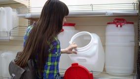 En ung kvinna väljer en stor vattenbehållare i supermarket stock video