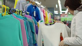 En ung kvinna väljer en stucken kofta för barnet i en supermarket stock video