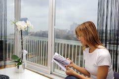 En ung kvinnaläsning en boka. Arkivfoton