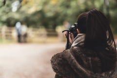 En ung kvinnlig caucasian fotograf tar en bild av ett par arkivbild