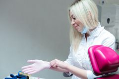 En ung kvinnlig doktor som förbereder sig för att arbeta och att sätta på skyddande handskar royaltyfri foto