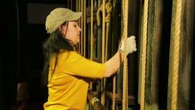 En ung kvinnlig etapparbetare i handskar sätter monteringen på lyftande mekanismen av en teatergardin på en kabel stock video