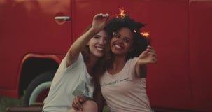 En ung kvinnlig för afrikan och hennes vän som köps med lockigt hår som ler spela med tomtebloss på picknicksammanträdet lager videofilmer