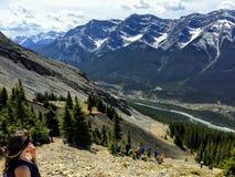 En ung kvinnlig fotvandrare som tycker om sikten av Rocky Mountains, medan fotvandra till överkanten av det mummelLing maximumet royaltyfria bilder
