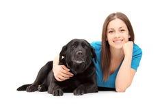 En ung kvinnlig som ligger och poserar med en svart hund Fotografering för Bildbyråer