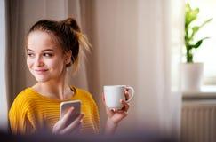 En ung kvinnlig student med att vila för kaffe och för smartphone arkivfoton
