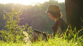 En ung kvinnlig student sitter i en parkera under ett träd och en läsning en bok Utbildning och läs- utomhus arkivfilmer