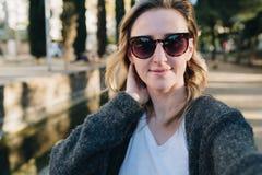 En ung le kvinna står i en parkera och gör en selfie Flickan i solglasögon tar bilder av henne arkivfoto