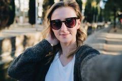 En ung le kvinna står i en parkera och gör en selfie Flickan i solglasögon tar bilder av henne fotografering för bildbyråer