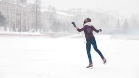 En ung le kvinnaskridskoåkning utanför tunga snowfall fotografering för bildbyråer