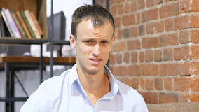 En ung ledsen olycklig ilsken och desperat affärsman i hans idérika kontor Arkivbild