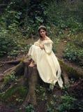 En ung ledsen prinsessa med mycket långt hår sitter på en stor stubbe av ett gammalt träd och väntar på hennes prins Flickan har  arkivfoto