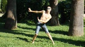 En ung lycklig grabb med en kal torso som dansar modern balett och går i en sommar, parkerar Långsam-Mo arkivfilmer