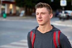 En ung lycklig grabb med problemhud som har gyckel, medan gå runt om sommarstaden arkivfoton