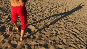 En ung lycklig grabb som dansar modern balett och wacking på en sandig strand på bakgrunden av havet Långsam-Mo stock video