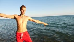 En ung lycklig grabb som dansar modern balett och wacking på en sandig strand på bakgrunden av havet Långsam-Mo lager videofilmer