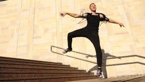 En ung lycklig grabb som dansar modern balett och wacking på trappan i gatan Långsam-Mo stock video