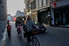 en ung lycklig le kvinna med rött hår rider en cykel ner gatan för att shoppa royaltyfria foton
