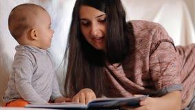 En ung lycklig moder ser hennes lilla son och ler En att bry sig moder läser en saga till hennes barnultrarapid stock video