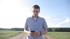 En ung man är gå och skriva ett meddelande på smartphonen arkivfilmer