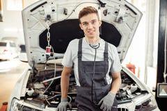 En ung man är på arbete på en bilservice royaltyfria foton