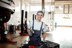 En ung man är på arbete, medan förbereda sig för att ändra ett gummihjul royaltyfri foto