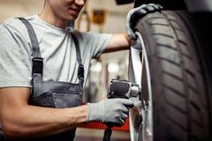 En ung man är på arbete som ändrar ett gummihjul på en lyftbil Medelunderhåll royaltyfri foto