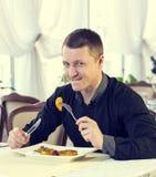 En ung man äter middag Arkivfoto