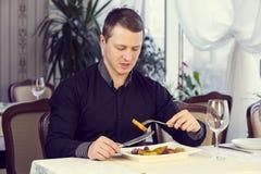En ung man äter middag Arkivfoton