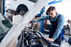 En ung man arbetar på en tjänste- station Mekanikern är förlovad, i att reparera bilen royaltyfri foto